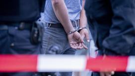мужчина в наручниках стоит за сигнальной лентой
