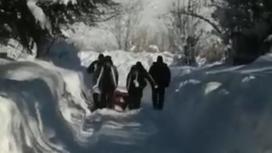 Люди несут гроб по снегу