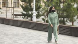 Девушка в зеленом костюме и черной маске идет по улице