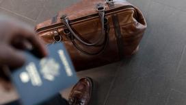 Человек держит в руках паспорт синего цвета