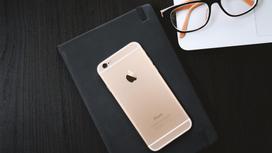 Смартфон на записной книге возле очков
