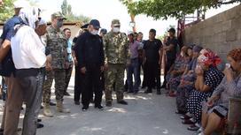 Бердибек Сапарбаев и военный говорят с гражданами