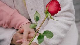 Женщина держит розу