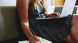 Девушка сидит с ноутбуком на коленях