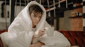 Мужчина, укрытый одеялом, держит кружку