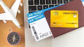 Игрушечный самолет стоит рядом с компьютером, паспортом, билетами, кредитной картой и компасом