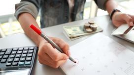 Работник отмечает день в календаре и держит кредитную карту
