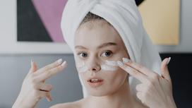 Девушка с полотенцем на волосах наносит крем на лицо