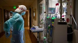 Медработница смотрит в окно больничной палаты