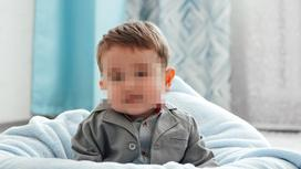Ребенок сидит на кровати