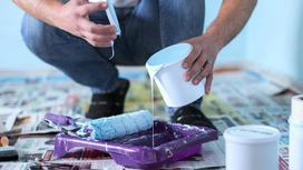 Мужчина наливает краску с побелки