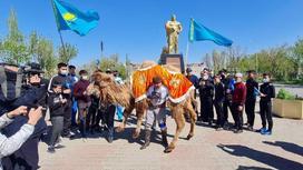 мужчина поднимает верблюда на площади