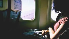 Девушка сидит в самолете