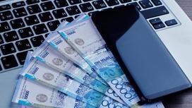 Деньги лежат на ноутбуке рядом с телефоном