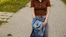 Девушка стоит на улице и держит в руках джинсовую куртку