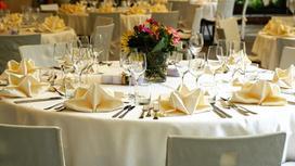 Столы, сервированные посудой и украшены букетами