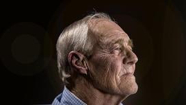 Пожилой мужчина стоит боком