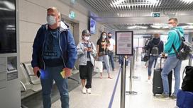 Пассажиры стоят в коридоре аэропорта