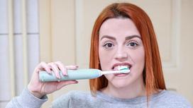 Рыжая девушка чистит зубы