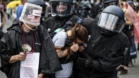 Полицейские ведут протестующую