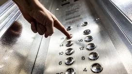 Человек нажимает на кнопку лифта