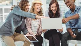 Люди смеются, глядя на экран ноутбука