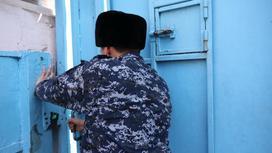 сотрудник колонии закрывает дверь