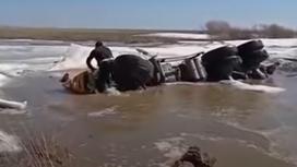 Мужчина пытается вызволить водителя тонущего грузовика