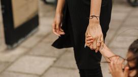 Женщина держит ребенка за руку