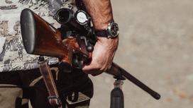 Мужчина держит ружье в руках