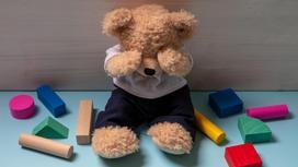 Плюшевый медведь сидит на полу рядом с фигурками, прикрыв морду лапами