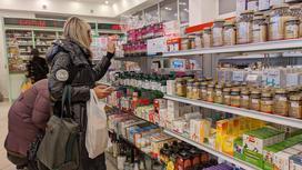 Женщина в аптеке выбирает лекарство