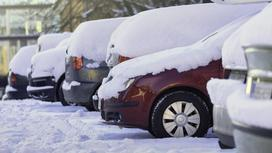 Заснеженные автомашины стоят на парковке