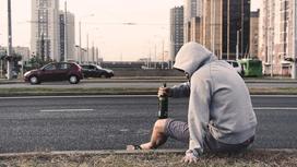 Мужчина сидит на дороге с алкоголем