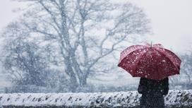 Человек стоит с зонтом под снегом