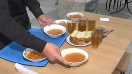 Тарелки с супом, ломтики хлеба и стаканы стоят на столе