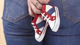 Женщина держит в руке детские кроссовки