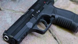 Пистолет лежит на каменной поверхности