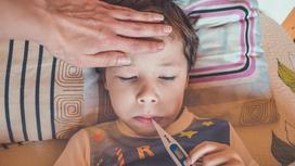 Ребенок держит термометр