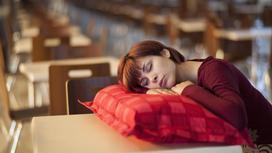Девушка спит за партой на подушке