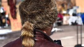 Человек в меховой шапке идет по улице