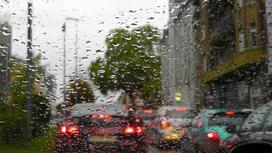 Автомобили на дороге на фоне стекла с каплями дождя