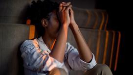 Девушка сидит в депрессии, держа руки у лица