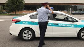 Полицейский в форме идет к служебному авто
