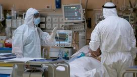 Врачи проверяют состояние пациента, лежащего на больничной койке