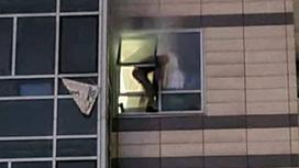 Мужчина вылезает из окна