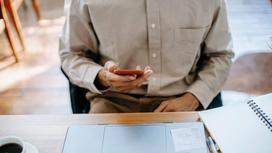 Мужчина сидит перед ноутбуком и держит телефон в руке