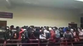 Толпа людей стоит, опершись на перила