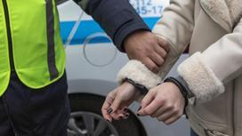 Полицейский держит за руку задержанную