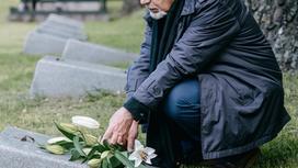 Пожилой мужчина возлагает цветы на могилу